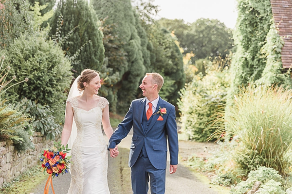 Bride and groom walking together, smiling hand in hand down a lane lined with green trees and borders